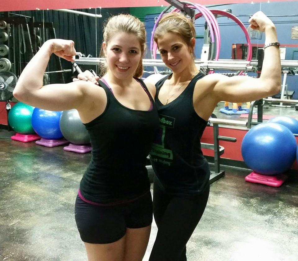 Sabrina and client flexing biceps